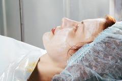 Testarossa con la crema di massaggio sul fronte Fotografia Stock Libera da Diritti