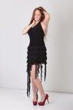 Testarossa graziosa in un vestito nero e nelle scarpe rosse Fotografia Stock Libera da Diritti