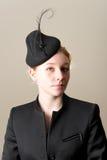 Testarossa in rivestimento nero e cappello messo le piume a Fotografia Stock
