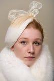 Testarossa seria in cappello bianco con l'arco e la pelliccia Fotografie Stock