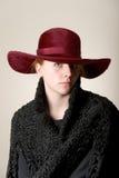 Testarossa seria in cappello marrone rossiccio e cappotto nero Fotografia Stock