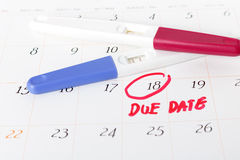 Teste de gravidez com o resultado positivo que encontra-se no fundo do calendário Fotografia de Stock