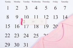 Teste de gravidez com resultado positivo e bodysuit para recém-nascido no calendário, esperando para o bebê Fotos de Stock Royalty Free