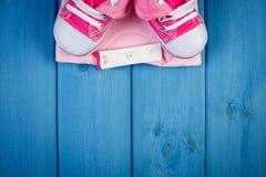 Teste de gravidez com resultado positivo e roupa para recém-nascido, esperando para o bebê, espaço da cópia para o texto Fotos de Stock