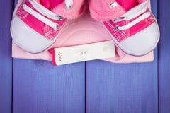 Teste de gravidez com resultado positivo e roupa para recém-nascido, esperando para o bebê, espaço da cópia para o texto Fotos de Stock Royalty Free