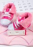 Teste de gravidez com resultado positivo e roupa para recém-nascido no calendário, esperando para o bebê Foto de Stock Royalty Free