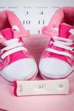 Teste de gravidez com resultado positivo e roupa para recém-nascido no calendário, esperando para o bebê Imagens de Stock Royalty Free