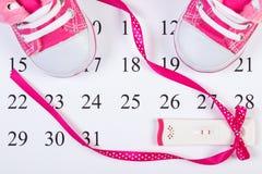 Teste de gravidez com resultado positivo e sapatas de bebê no calendário, esperando para o bebê Imagem de Stock
