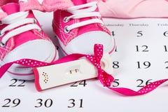 Teste de gravidez com resultado positivo e sapatas de bebê no calendário, esperando para o bebê Fotografia de Stock Royalty Free