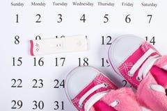 Teste de gravidez com resultado positivo e sapatas de bebê no calendário, esperando para o bebê Foto de Stock Royalty Free