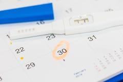 Teste de gravidez positivo com calendário Fotografia de Stock