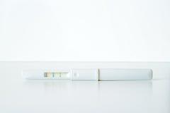 Teste de gravidez positivo plástico branco no fundo branco Foto de Stock Royalty Free
