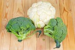 Teste dei broccoli e del cavolfiore sulla tavola rustica di legno fotografia stock libera da diritti