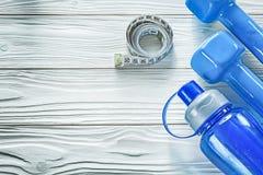 Teste di legno che misurano la bottiglia di acqua del nastro su forma fisica co del bordo di legno Fotografia Stock