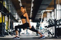 Teste di legno di sollevamento della bella donna di forma fisica Ragazza sportiva di forma fisica che si esercita nella palestra Immagine Stock