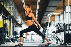 Teste di legno di sollevamento della bella donna di forma fisica Ragazza sportiva di forma fisica che si esercita nella palestra Immagine Stock Libera da Diritti