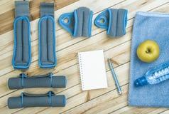 Teste di legno, pesi, asciugamano, acqua, taccuino Immagine Stock