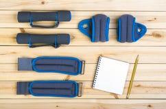 Teste di legno, pesi, taccuino Fotografie Stock Libere da Diritti