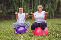 Teste di legno senior della tenuta delle coppie mentre sedendosi sulla palla di forma fisica dentro Fotografia Stock Libera da Diritti