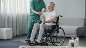 Teste di legno di sollevamento dell'uomo senior, sedentesi in sedia a rotelle al centro di riabilitazione Fotografia Stock Libera da Diritti