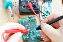 Teste o trabalho de reparo na placa de circuito impresso eletrônica Imagem de Stock