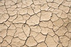Teste padrão à terra do fundo do deserto rachado seco da lama Imagens de Stock