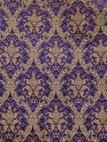 Teste padrão barroco dourado em um fundo violeta papel de parede, tela, tela do deco, tela da mobília fotos de stock