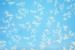 Teste padrão bonito do gelo no vidro em um fundo azul foto de stock