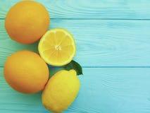 Teste padrão cítrico suculento do ingrediente dos limões e das laranjas no frescor de madeira azul fotos de stock royalty free