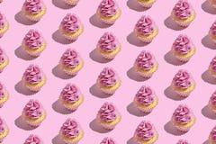 Teste padrão colorido do queque no fundo cor-de-rosa pastel Conceito m?nimo criativo do partido fotografia de stock