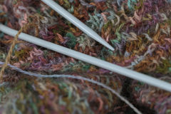 Teste padrão colorido feito malha de lãs do fio com agulhas de confecção de malhas Foto de Stock Royalty Free