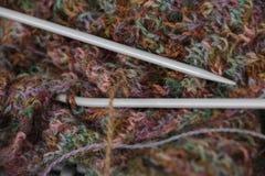 Teste padrão colorido feito malha de lãs do fio com agulhas de confecção de malhas Fotos de Stock