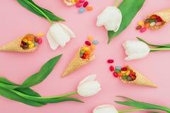 Teste padrão com os doces de açúcar brilhantes em cones do waffle e nas flores brancas no fundo cor-de-rosa Configuração lisa, vi Fotografia de Stock Royalty Free