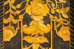 Teste padrão das flores cinzeladas na porta de madeira imagens de stock royalty free