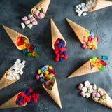 Teste padrão de doces sortidos brilhantes coloridos em cones do waffle no fundo escuro Configuração lisa, vista superior Imagem de Stock