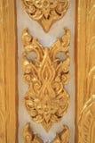 Teste padrão de flor dourado na parede branca Fotografia de Stock Royalty Free