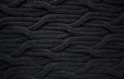 Teste padrão de lã preto da malha do cabo imagens de stock