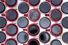 Teste padrão do café preto em umas canecas vermelhas e brancas Foto de Stock Royalty Free