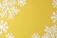 Teste padrão do floco de neve do Natal com espaço da cópia do quadro no fundo pastel amarelo Configuração lisa Conceito mínimo imagem de stock