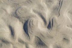 Teste padrão encaracolado, ondulado da areia na praia Fotografia de Stock Royalty Free