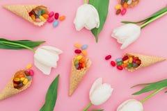 Teste padrão feito de doces brilhantes coloridos em cones do waffle e nas flores brancas no fundo cor-de-rosa Configuração lisa,  Fotografia de Stock Royalty Free