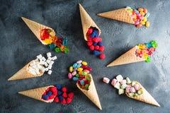 Teste padrão feito de doces sortidos brilhantes coloridos em cones do waffle no fundo escuro Configuração lisa, vista superior Foto de Stock