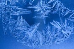 Teste padrão gelado azul de flocos de neve aguçado na janela do inverno fotos de stock