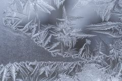 Teste padrão gelado do gelo do inverno com os flocos de neve aguçado graciosos na janela fotografia de stock