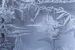 Teste padrão gelado do inverno com partes afiadas a céu aberto na janela congelada fotos de stock