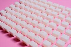 Teste padrão geométrico com açúcar refinado em um fundo cor-de-rosa Foto de Stock