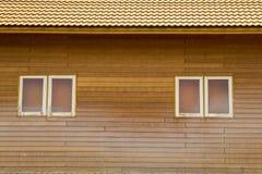 Teste padrão marrom velho do telhado de telhas da argila com as janelas pequenas em wal de madeira Fotografia de Stock