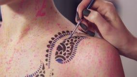 Teste padrão mestre da pintura no corpo do ` s da menina que usa a escova e cores diferentes Tiro Slowmotion vídeos de arquivo