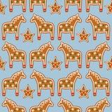 Teste padrão sem emenda com as cookies do pão-de-espécie do Natal - estrelas e cavalos do Xmas no fundo azul Ilustração Stock