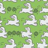 Teste padrão sem emenda do vetor com coelhos e trevo em um fundo verde Fotografia de Stock Royalty Free